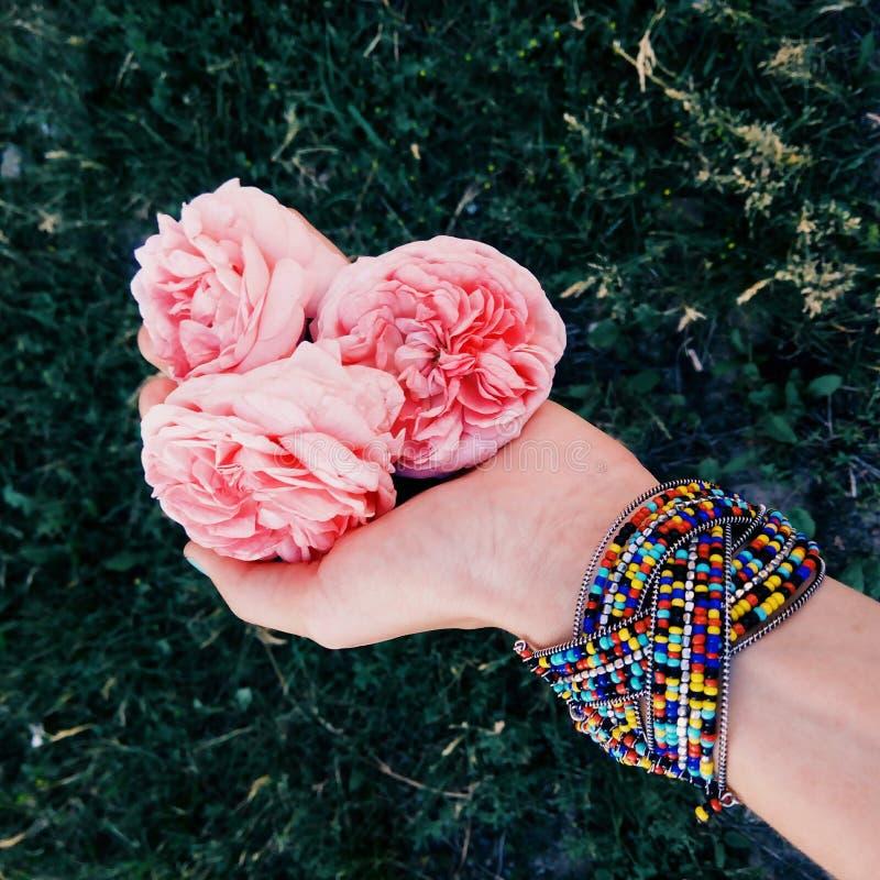 Braccialetto indiano luminoso e petali rosa delicati immagini stock