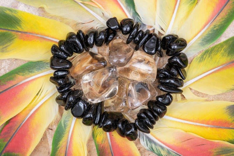 Braccialetto nero della TORMALINA e pietre CITRINE naturali ruzzolate in mezzo ad un cerchio delle piume variopinte del pappagall immagini stock