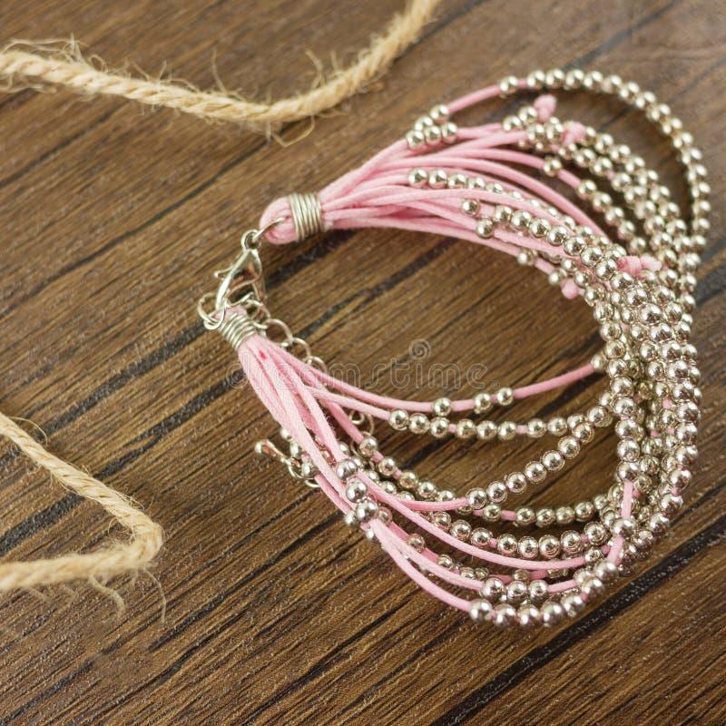 Braccialetto rosa su fondo di legno immagine stock
