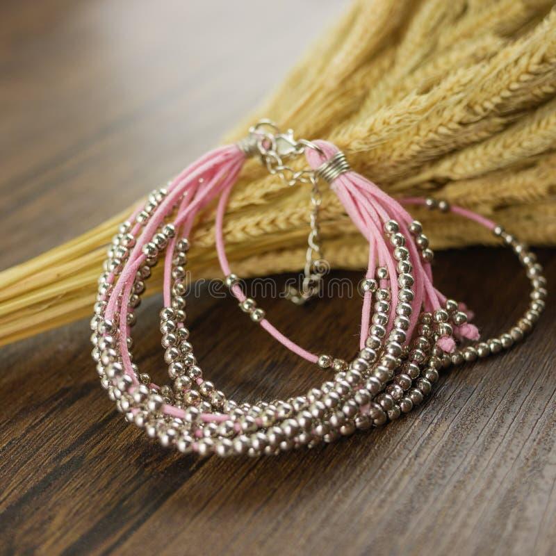Braccialetto rosa su fondo di legno fotografia stock libera da diritti