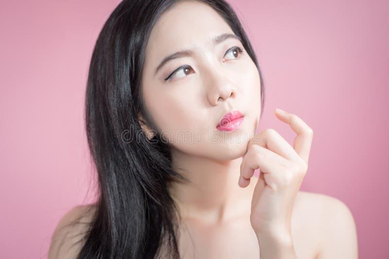Braccio asiatico dell'incrocio della donna dei capelli lunghi giovani bei e dito del punto verso l'alto isolato sopra fondo rosa  immagine stock libera da diritti