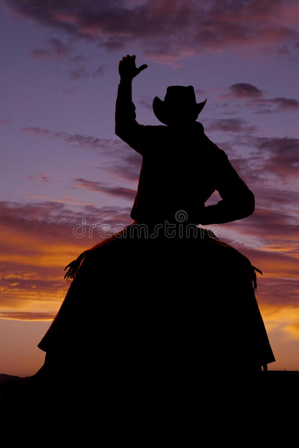 Braccio del cavallo della parte anteriore della siluetta del cowboy su fotografia stock libera da diritti