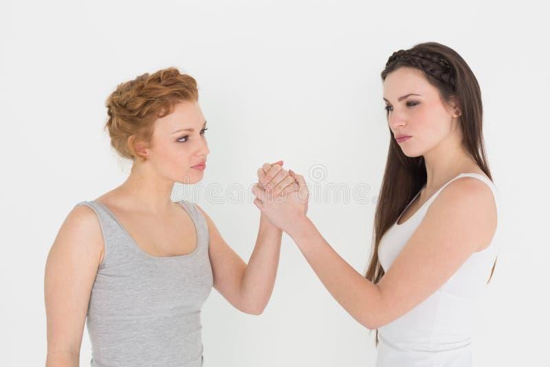 Braccio di ferro femminile serio di due un giovane amici immagine stock libera da diritti