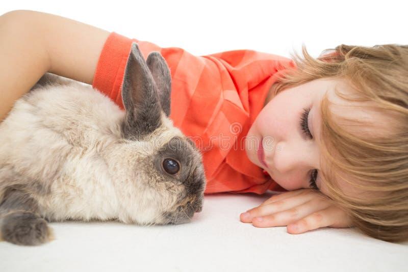 Braccio di menzogne del ragazzo sveglio intorno al coniglietto fotografia stock