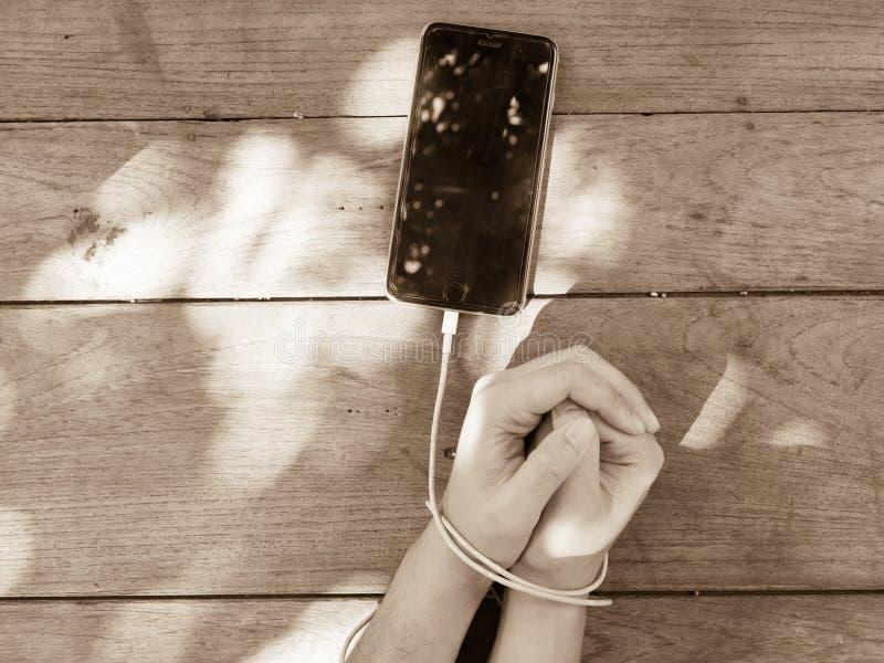 Braccio di schiavitù di Smartphone dalla linea del commutatore fotografia stock