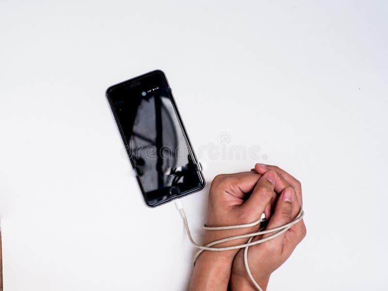 Braccio di schiavitù di Smartphone dalla linea del commutatore fotografie stock
