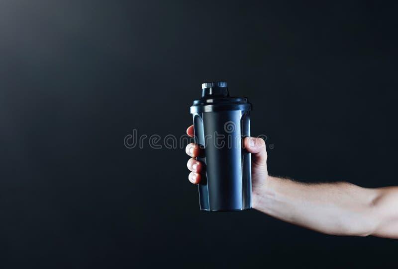 Braccio di uno sportman muscolare con un agitatore nero su un backgr scuro fotografie stock libere da diritti