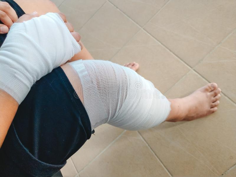Braccio e gamba di incidente dell'uomo del fondo di sanità con la fasciatura Im immagini stock libere da diritti