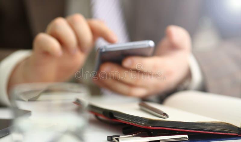Braccio maschio nella penna del telefono e dell'argento della tenuta del vestito fotografia stock libera da diritti