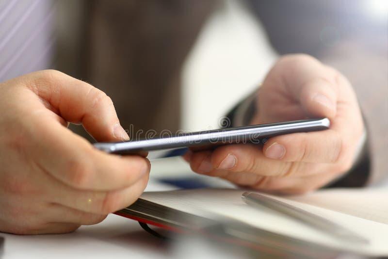 Braccio maschio nella penna del telefono e dell'argento della tenuta del vestito immagini stock libere da diritti
