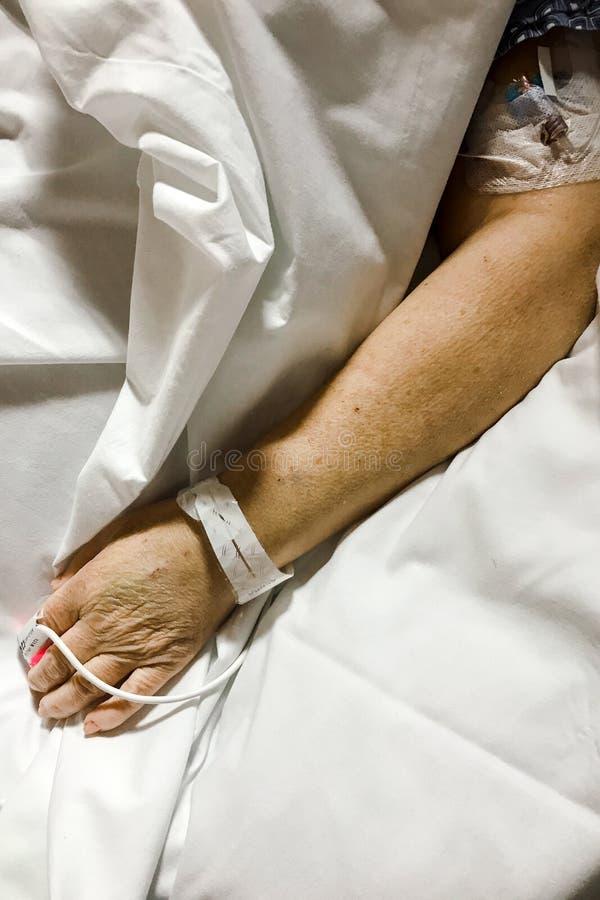 Braccio paziente del ` s su un lenzuolo in ospedale fotografia stock libera da diritti