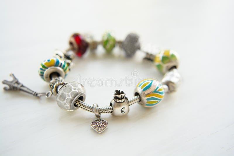 Bracelet avec beaucoup d'accessoires, chance, argent, un hibou photographie stock libre de droits