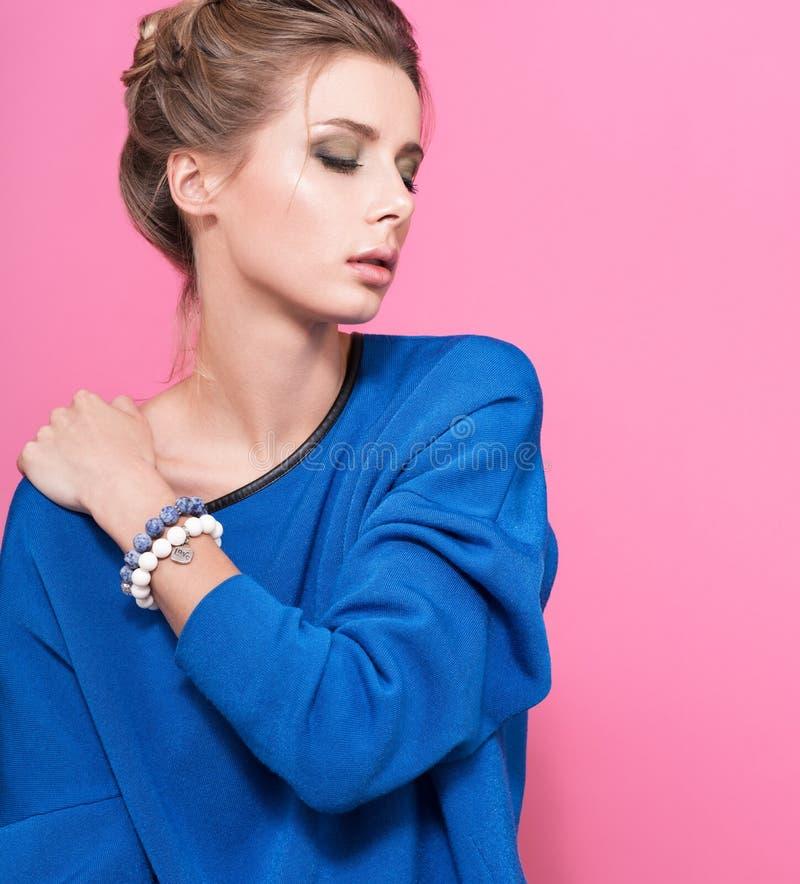 Bracelet avec des perles en main Verticale de belle jeune femme avec les yeux fermés photographie stock libre de droits