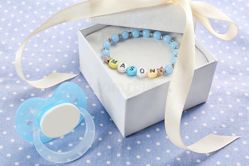 Bracelet avec le MAÇON de nom de bébé dans le boîte-cadeau et la tétine photographie stock libre de droits