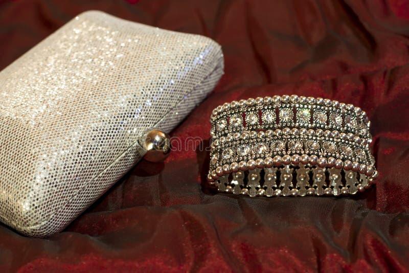 Bracelet avec les pierres claires et le sac d'embrayage argenté brillant Accessoires élégants Bijoux pour la robe de soirée photographie stock libre de droits