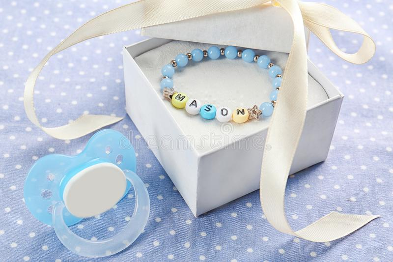 Bracelet with baby name MASON in gift box and pacifier royalty free stock photography