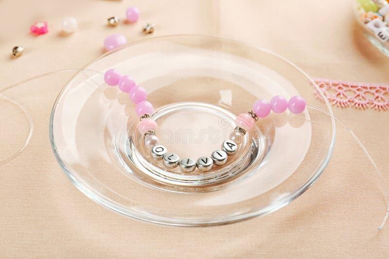 Bracelet with baby name OLIVIA stock photo