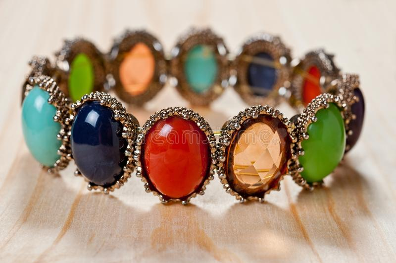 Bracelet of bright colored stones on a wooden background stock photo