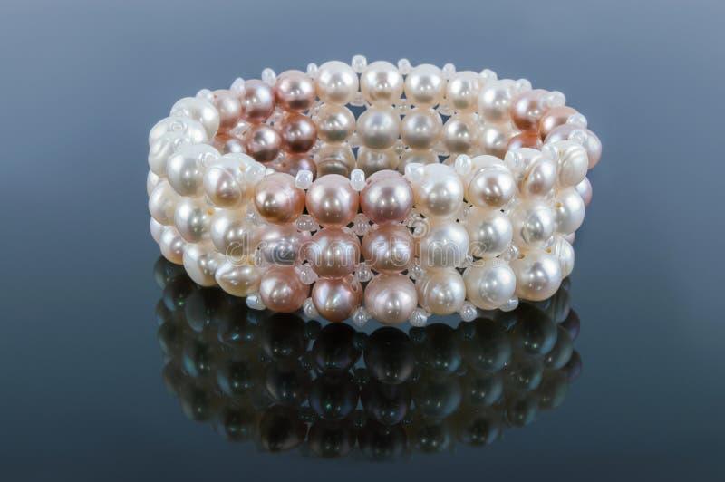 Bracelet des perles avec la réflexion sur un gris image stock