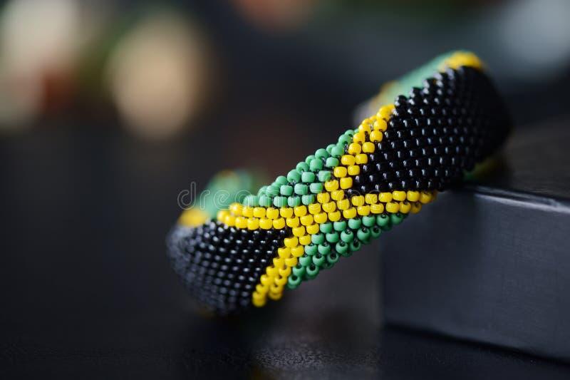 Bracelet jamaïcain de crochet de perle de drapeau sur un bakground foncé photographie stock
