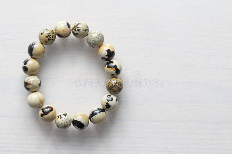 Bracelet from a natural landscape jasper. Bracelet made of natural stones on a white background. Jewelry made of natural stones. Copy space for your text royalty free stock image