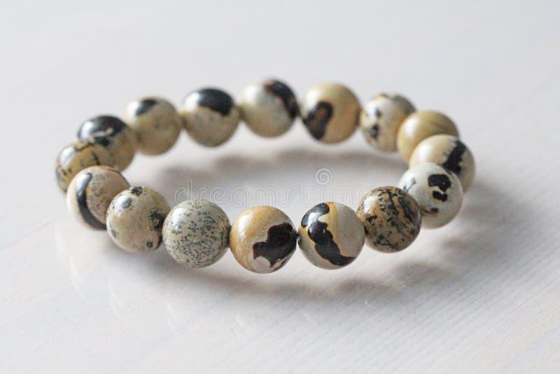 Bracelet from a natural landscape jasper. Bracelet made of natural stones on a white background. Jewelry made of natural stones. Copy space for your text stock image