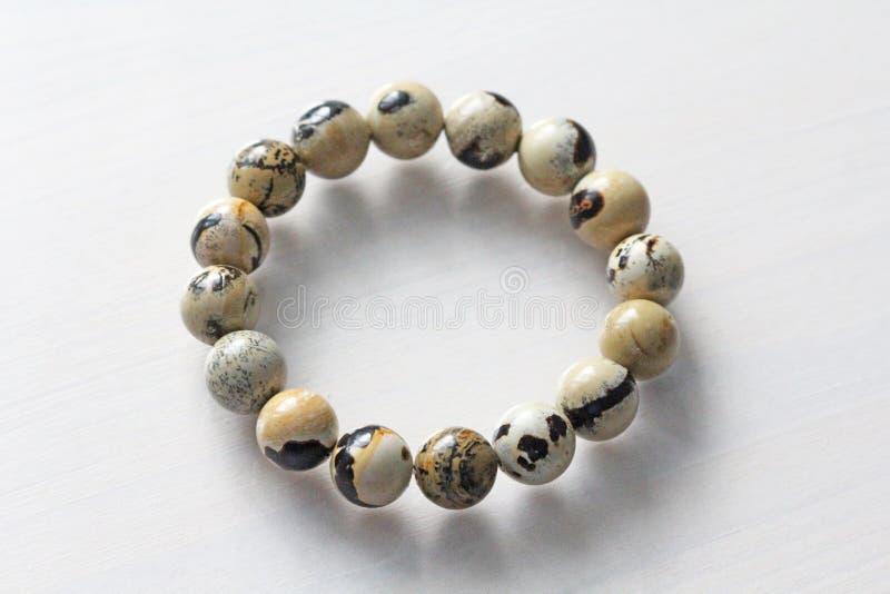 Bracelet from a natural landscape jasper. Bracelet made of natural stones on a white background. Jewelry made of natural stones. Copy space for your text stock photo
