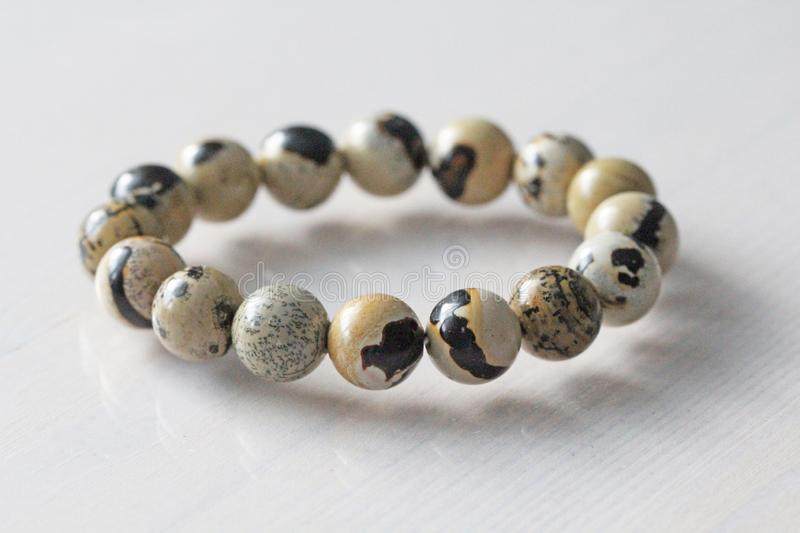 Bracelet from a natural landscape jasper. Bracelet made of natural stones on a white background. Jewelry made of natural stones. Copy space for your text royalty free stock photos