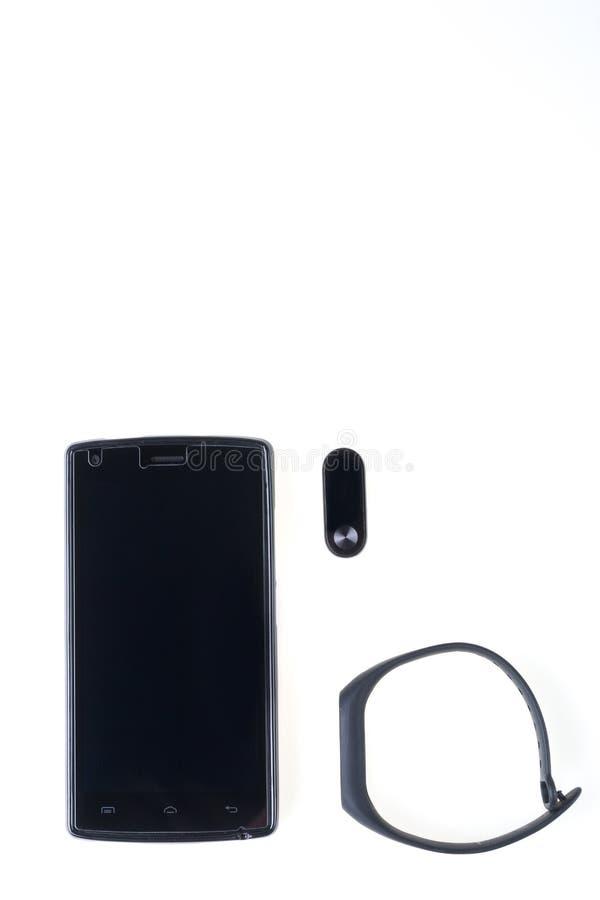 Bracelet noir et smartphone de forme physique d'isolement sur le fond blanc images stock