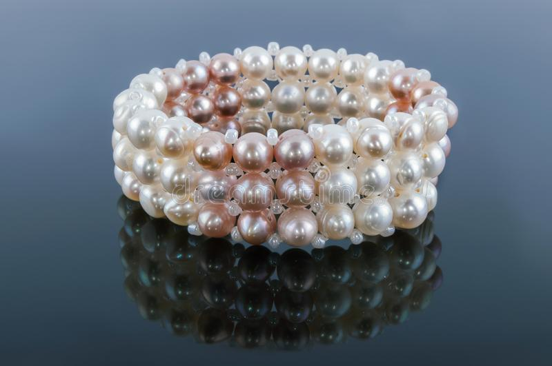 Bracelet of pearls with reflection on a gray. Background stock image