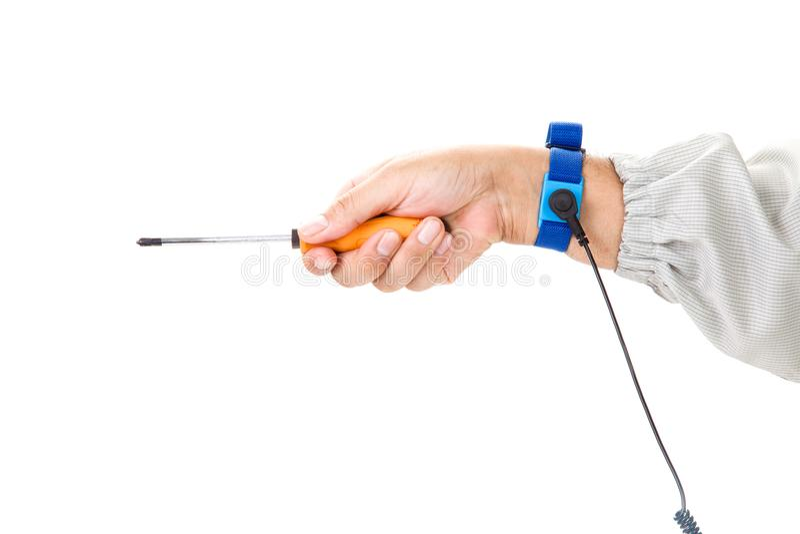 Bracelet sur la main d'un homme portant le tissu d'ESD tenant un screwd photographie stock libre de droits