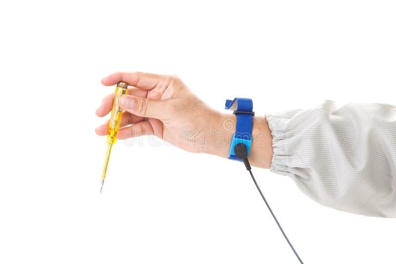 Bracelet sur la main d'un homme portant le tissu d'ESD tenant un screwd photo libre de droits