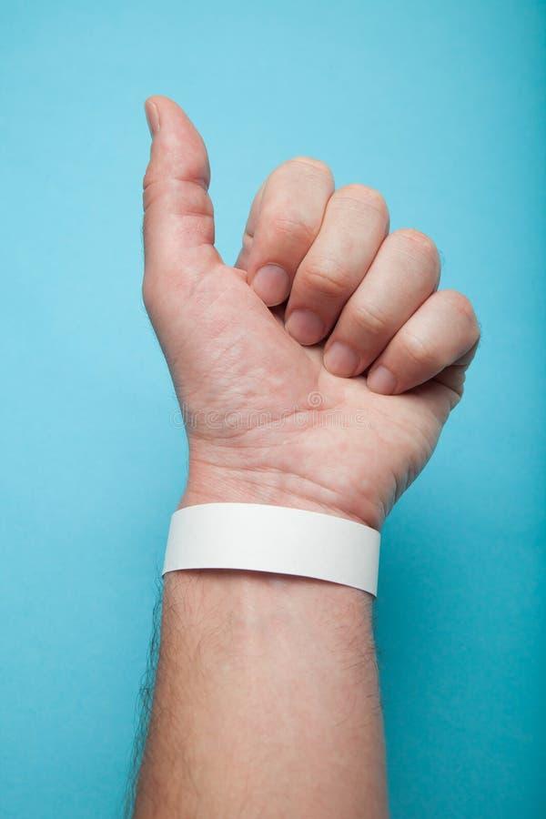 Bracelet vide de maquette sur la main de l'homme, d'isolement sur le fond bleu Bracelet de papier de concert photos stock