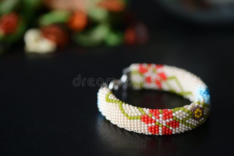 Bracelete bege com cópia floral em um fundo escuro imagens de stock