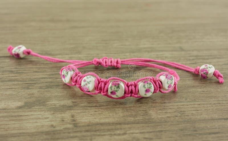 Bracelete cor-de-rosa no fundo de madeira imagem de stock