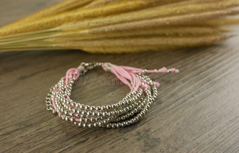 Bracelete cor-de-rosa no fundo de madeira fotografia de stock royalty free