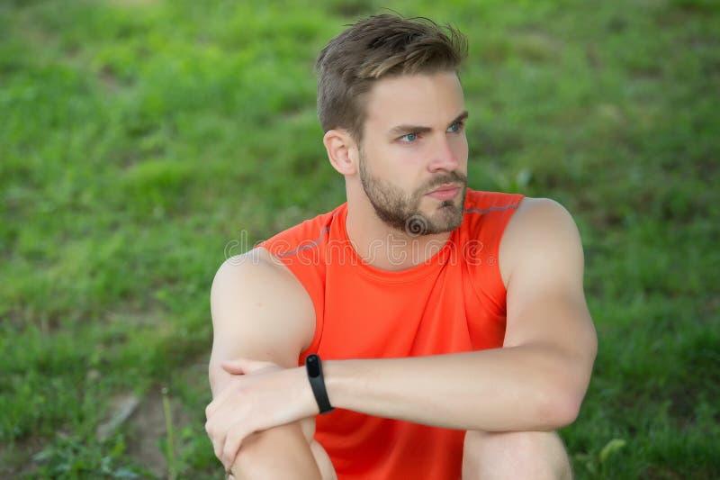 Bracelete do podômetro do desgaste do atleta disponível O homem atlético relaxa na grama verde Verificando resultados do exercíci imagens de stock royalty free