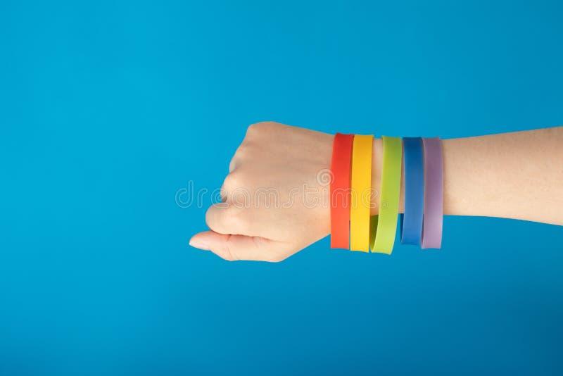 Bracelete do punho da bandeira LGBT do arco-íris na mão fêmea no fundo azul fotografia de stock