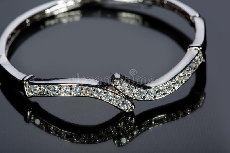 Bracelete dourado com as pedras preciosas no cinza imagens de stock royalty free