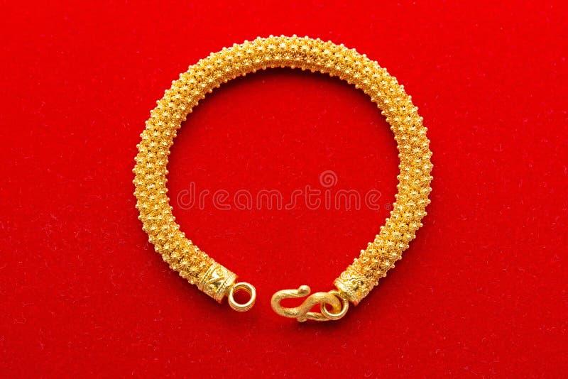 Bracelete dourado no fundo vermelho imagem de stock royalty free