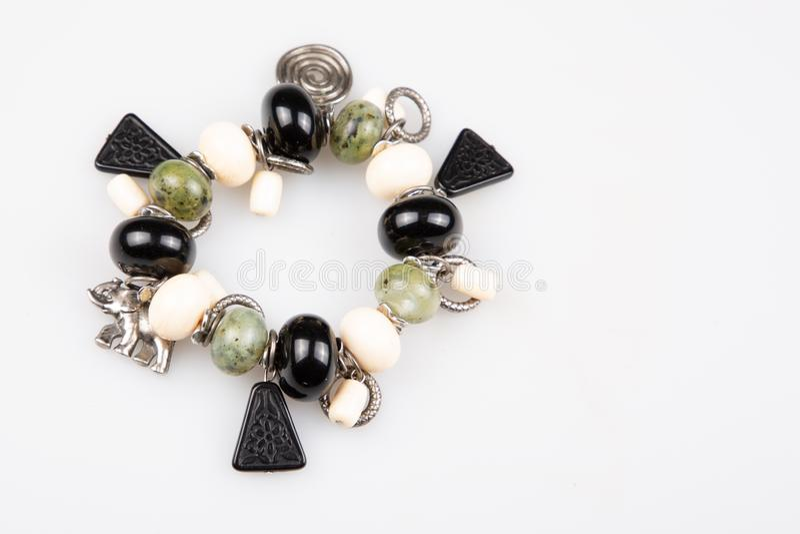 Bracelete frisado feito a mão com as bolas brancas e verdes pretas das pedras no fundo branco imagens de stock