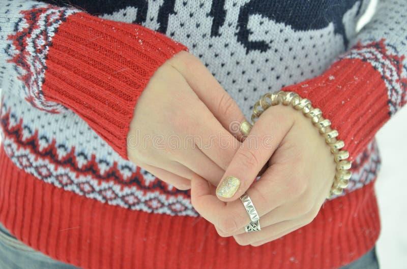 Bracelete no close-up da mão do ` s da menina Fundo da camiseta do inverno fotos de stock royalty free