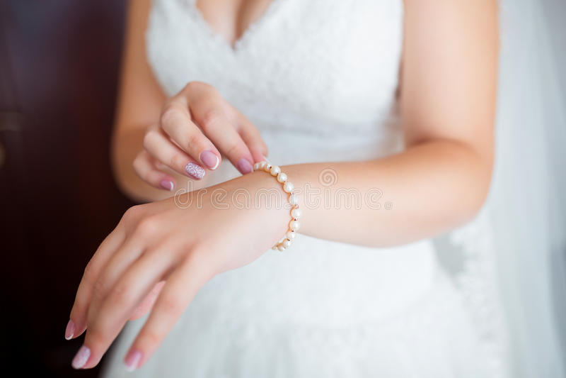 Bracelete vestindo da pérola da mulher bonita em sua mão fotos de stock