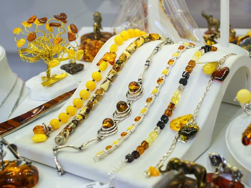Braceletes ambarinos Báltico da joia em um suporte branco na mostra de uma ourivesaria Âmbar nos braceletes e nos anéis de prata foto de stock