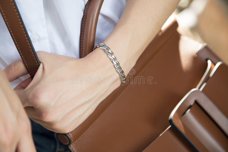 Braceletes de aço inoxidável do roupa de senhora e saco marrom fotografia de stock royalty free