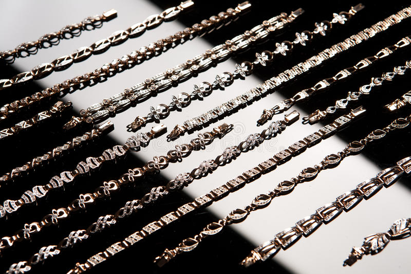 Braceletes dourados em um vidro foto de stock royalty free