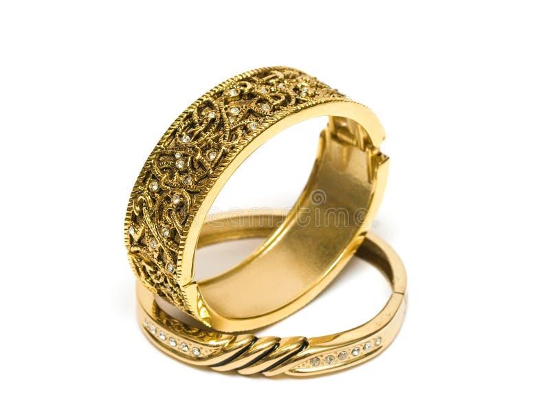Braceletes dourados isolados no branco fotos de stock royalty free