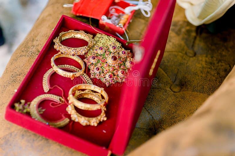 Braceletes e anéis dourados bonitos na cama Pulseira e braceletes do ouro do casamento fotografia de stock royalty free