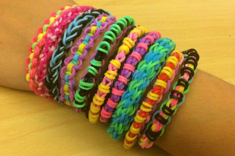 Bracelets de bande de métier à tisser sur le bras de filles photo libre de droits