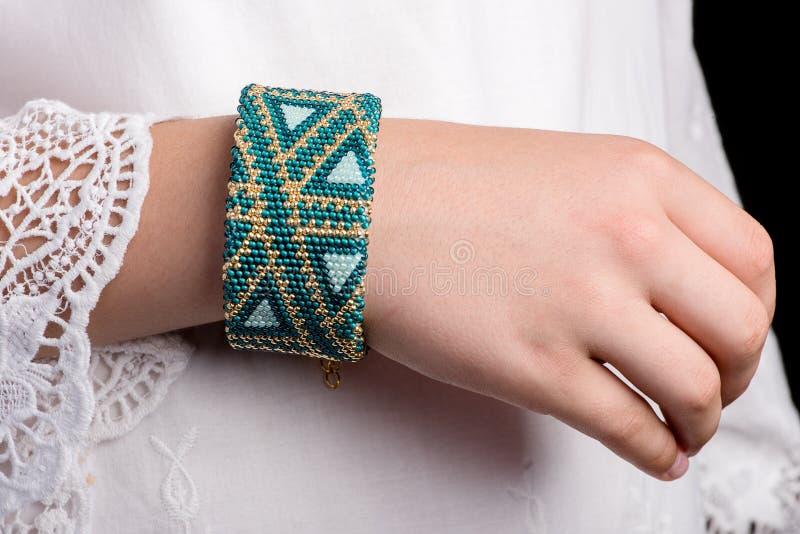 Bracelets de métier à tisser sur des mains de jeune fille photos stock